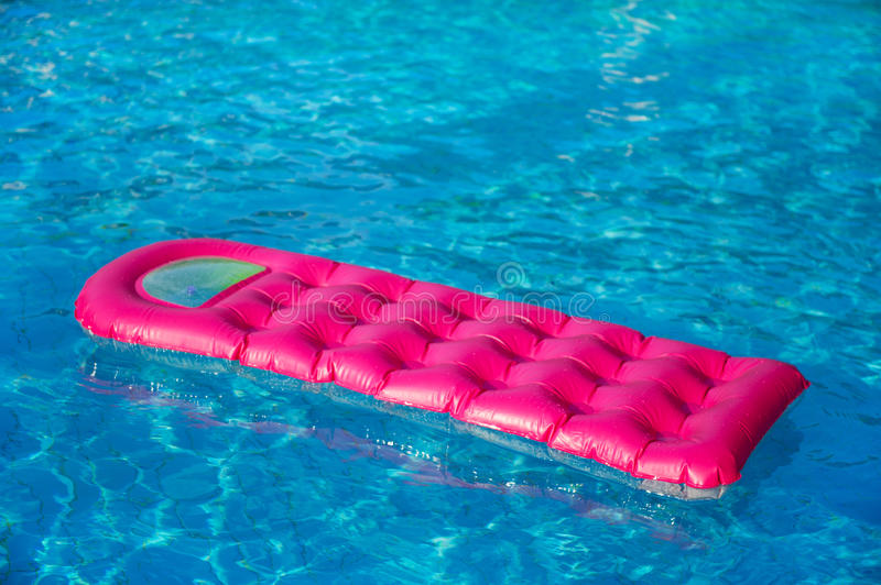 Floating air mattress. Floating pink and green air mattress in swimming pool stock photo