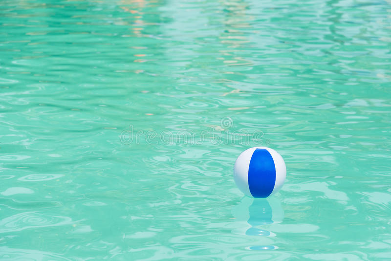Floating blue and white beachball in swimming pool. stock photos