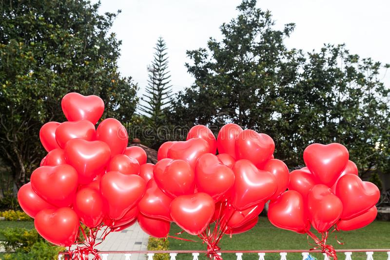 A floating bouquet of red, heart-shaped balloons royalty free stock photos