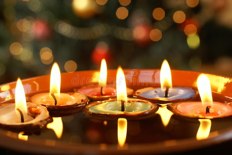 Floating candles. Candles in nutshells floating on water with Christmas background stock photos