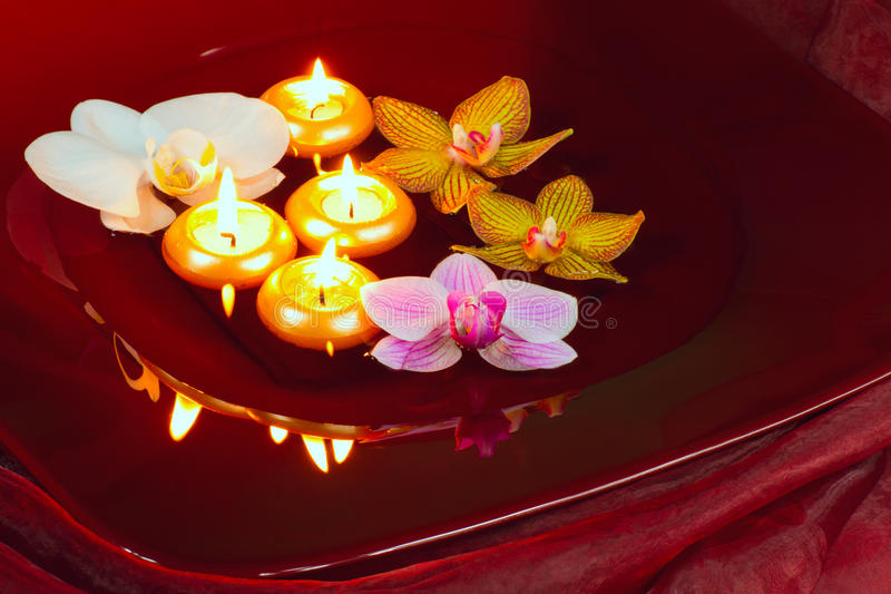 Floating candles and orchids stock photography
