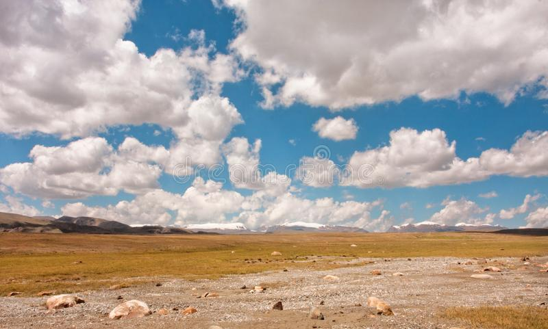 Floating clouds in blue sky over mountains and landscape. Bright morning on high attitude. Floating clouds in blue sky over mountains and beautiful landscape royalty free stock image