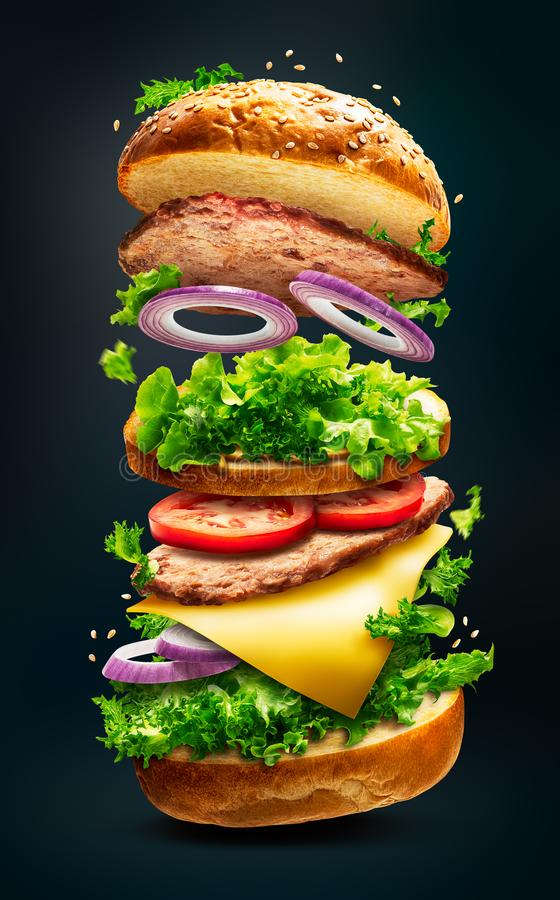 Floating burger isolated. Floating delicious burger with flying ingredients isolated on dark background with clipping path royalty free stock image