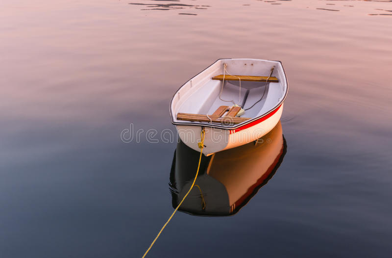 Floating dinghy. A floating dinghy on calm waters during sunset royalty free stock image