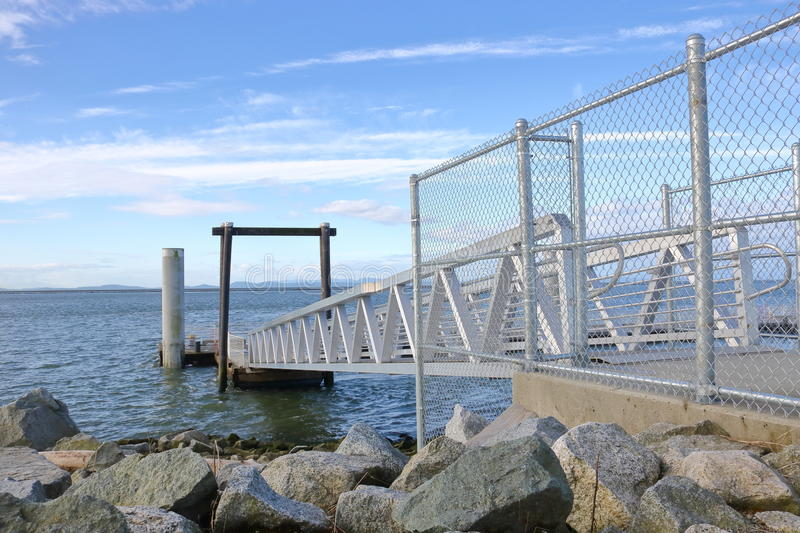 Floating Dock and Walkway. A metal walkway extends out over the water where its attached to a floating dock royalty free stock photos