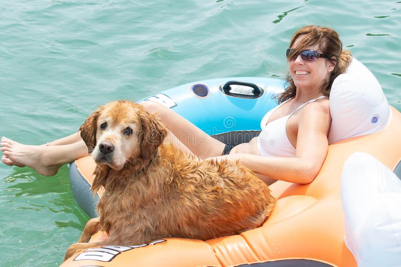 Happy woman floating with golden retriever dog on a lake royalty free stock photography