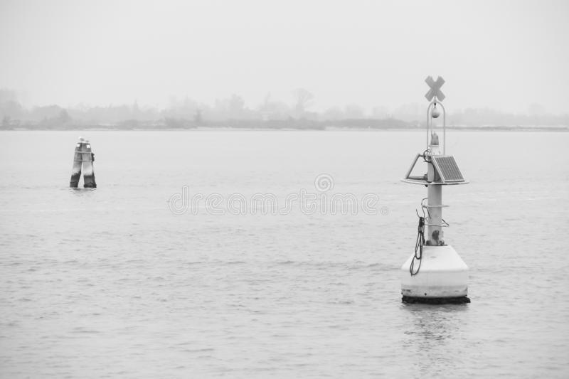 Floating marine light signs with solar pannel in the lagoon, black and white effect royalty free stock images