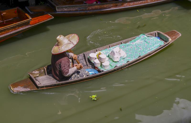 Floating market and old woman. Sell bamboo, sells fruits paddling in a dirty river stock images