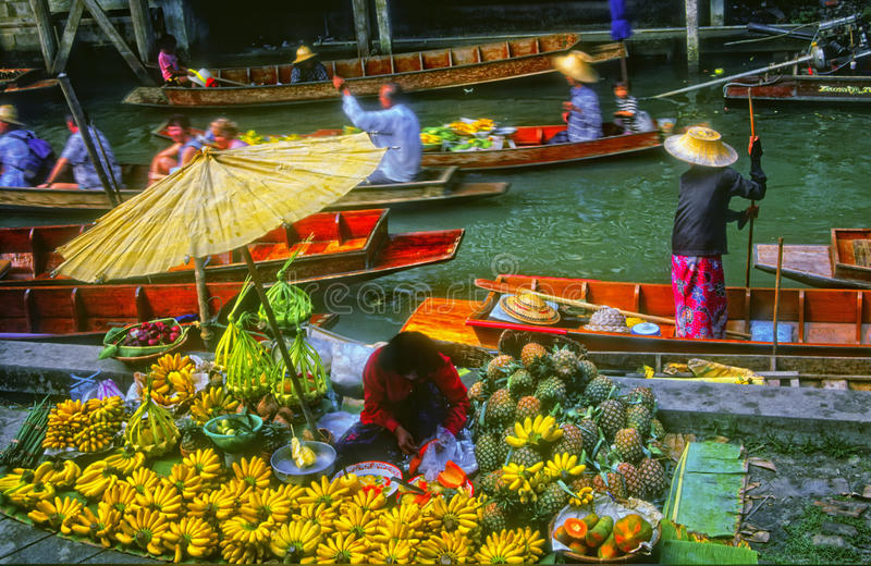 Floating Market, Thailand. A woman stands paddling a boat and another woman sells her fruits, including bananas, pineapples and melons, at a local floating