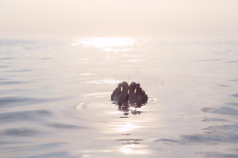 Floating med feet in serene sea water in sunset royalty free stock images