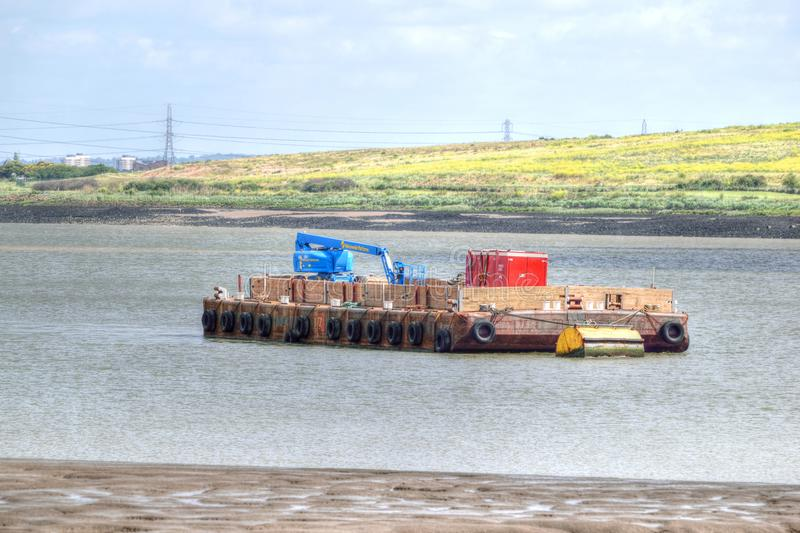 Floating pontoon with construction plant moored on River Thames, Kent, United Kingdom. Floating pontoon with height access equipment and power generator moored stock photos