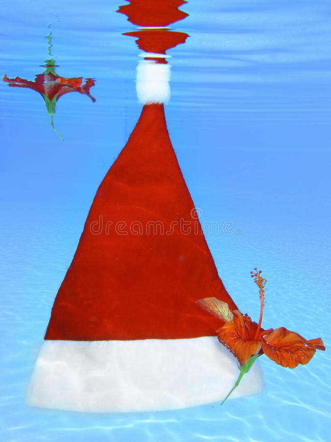 Floating Santa Hat. With tropical hibiscus flowers royalty free stock image