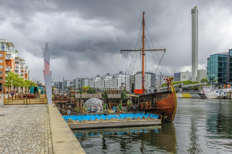 Floating thai restaurant THAIBOAT ih shape of vintage viking ship with own artificial mini beach on a raft on Hammarby canal. royalty free stock photos