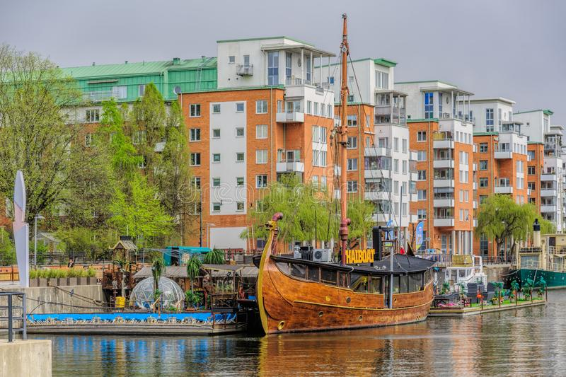 Floating thai restaurant THAIBOAT ih shape of vintage viking ship with own artificial mini beach on a raft on Hammarby canal. stock image