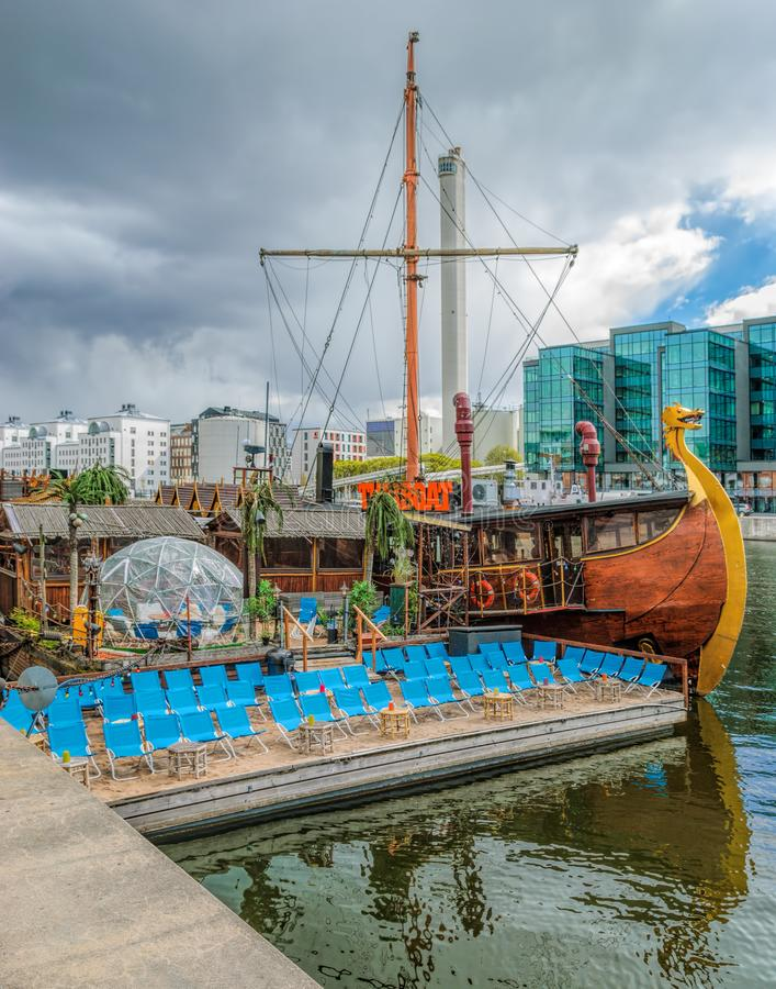 Floating thai restaurant THAIBOAT ih shape of vintage viking ship with own artificial mini beach on a raft on Hammarby canal. royalty free stock images