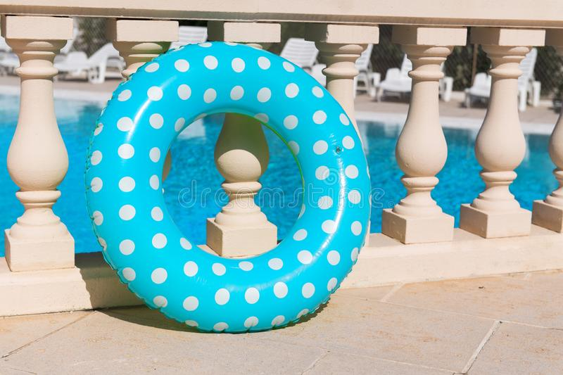 Floating toy for swimming pool. Floating ring toy in blue and green with swimming pool royalty free stock image