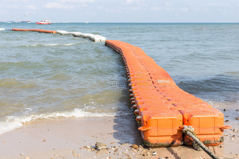 Floating walk way pontoon in the sea. Red floating walk way pontoon in the sea stock photo
