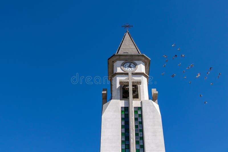 Pigeons flying around the clock tower of the chapel of Nuestra Senora de Bonanza in El Paso, La Palma, Canary Islands, Spain stock images