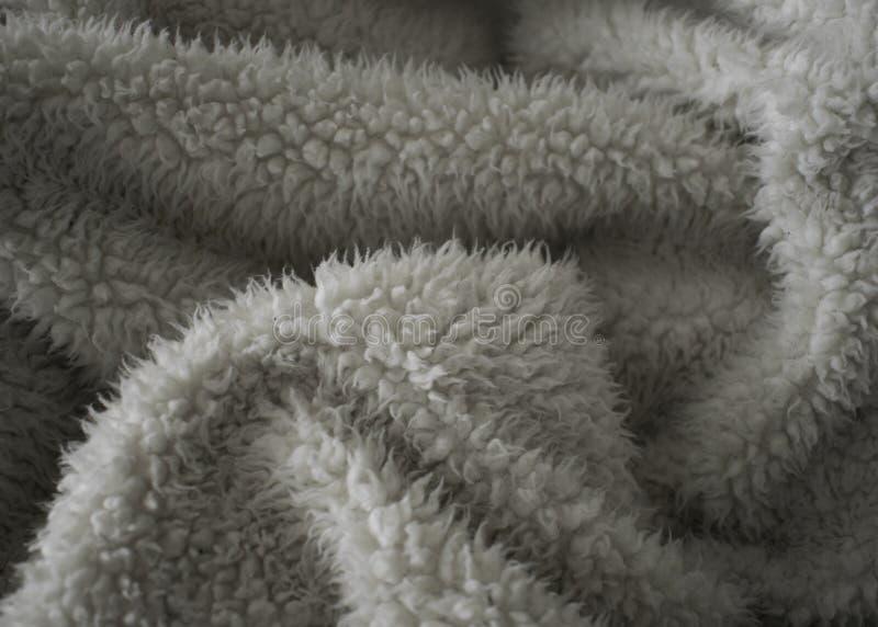 Flockige Falten in der weichen beige Decke lizenzfreies stockbild