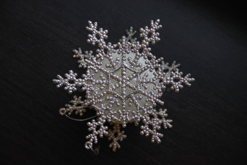 Floco de neve bonito do brilho do Natal no close up de superfície de madeira escuro imagens de stock royalty free