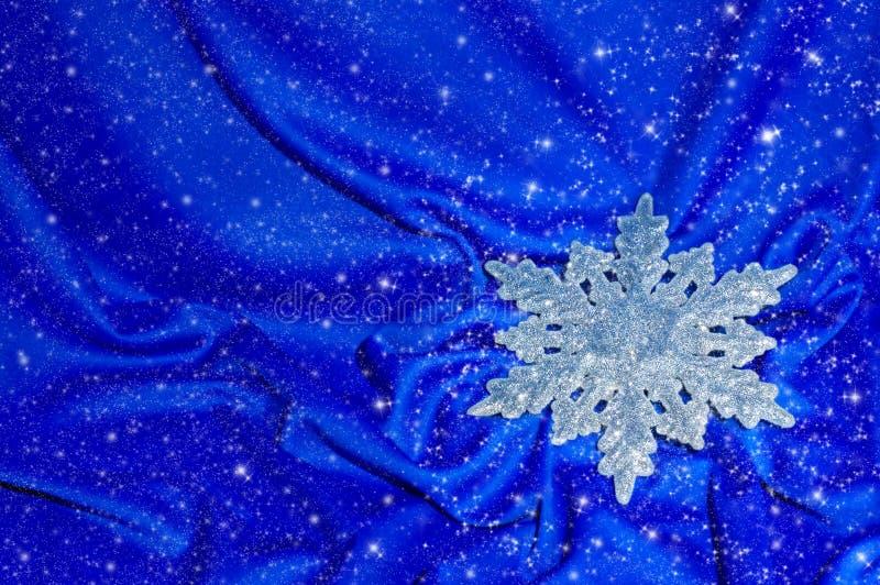Floco de neve em uma seda azul com sparkles imagens de stock