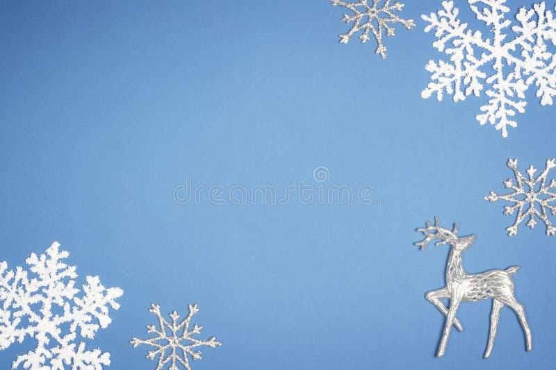 Flocon de neige blanc de décoration sur le fond bleu Vue supérieure de cerfs communs de Noël photo libre de droits