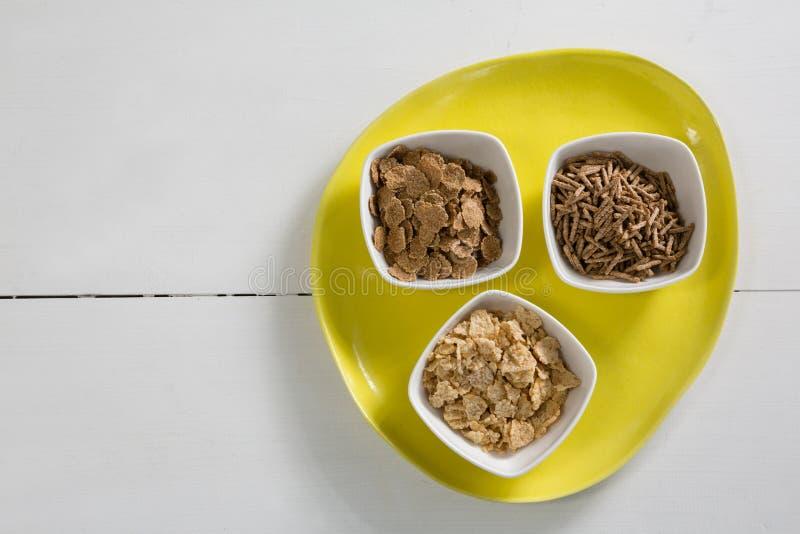 Flocons de blé et bâtons de son de céréale dans la cuvette image stock