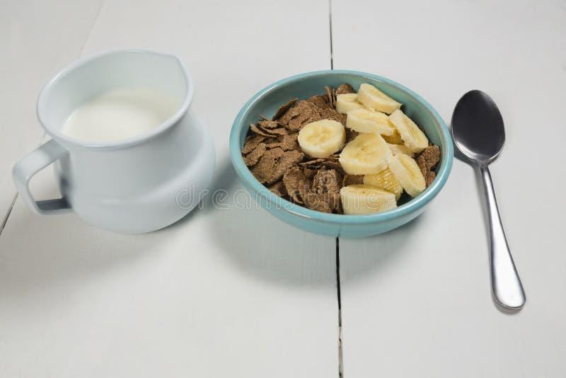 Flocons de blé et tranche de banane dans la cuvette avec la cruche de lait image stock