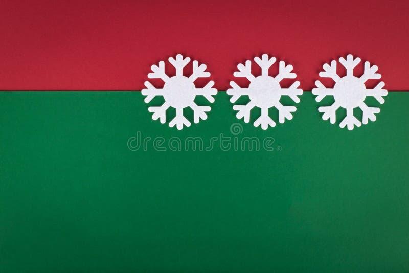 Flocons de neige blancs décoratifs sur le fond vert rouge photographie stock libre de droits