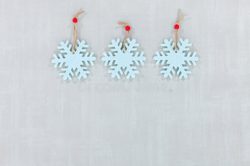 Flocons de neige bleu-clair de feutre sur un fond texturisé gris pâle avec l'espace pour la copie image stock