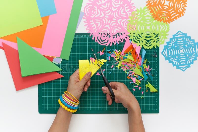 Flocons de neige de papier coloré Ciseaux et tapis de coupe photographie stock
