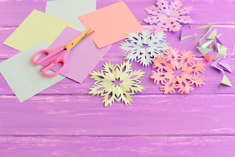 Flocons de neige de papier colorés, feuilles de papier coloré et chute, ciseaux sur le fond en bois lilas images libres de droits