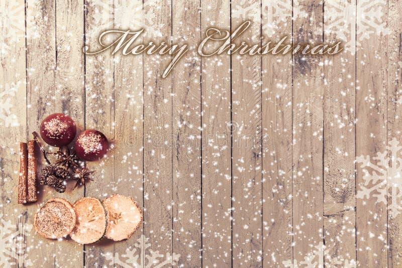 Flocons de neige sur un fond en bois avec des fruits de Noël et Noël des textes le Joyeux photo stock