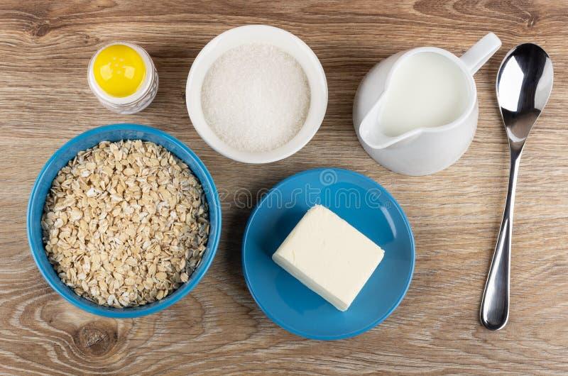 Flocos da aveia na bacia, açúcar, sal, jarro do leite, manteiga nos pires, colher na tabela Vista superior fotos de stock