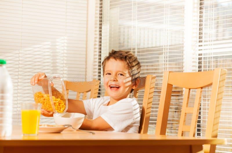 Flocos de milho de derramamento do menino que fazem o café da manhã saudável imagem de stock royalty free