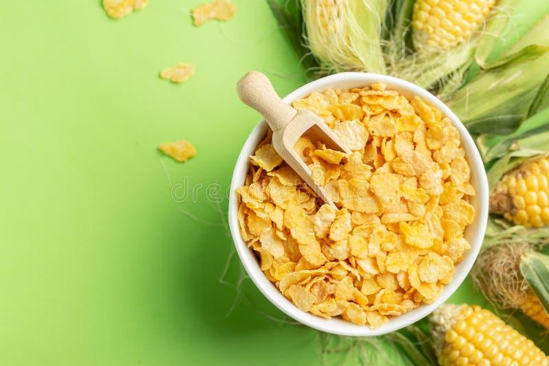Flocos de milho e espigas de milho sobre o fundo verde, apresentação saudável do conceito do alimento fotografia de stock