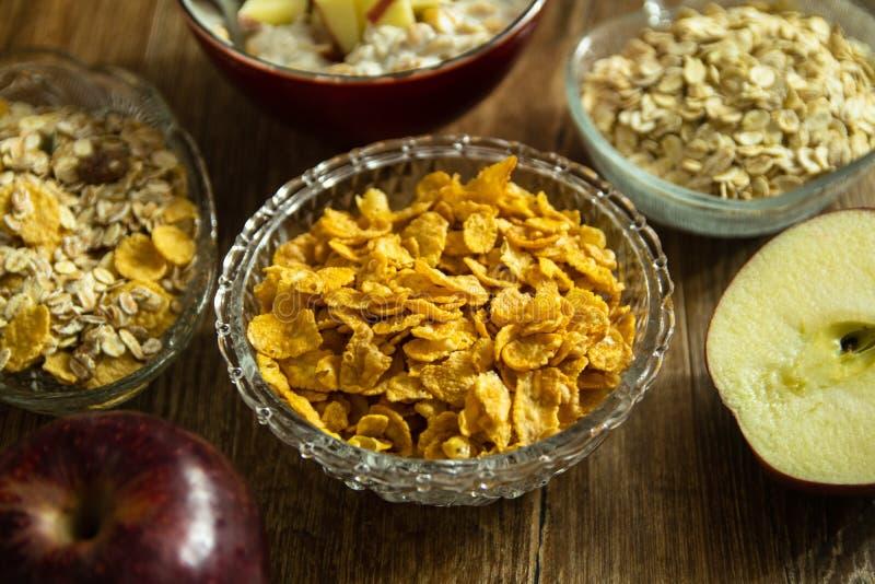 Flocos de milho em uma bacia de cristal, em uma maçã orgânica vermelha fresca e no outro alimento saudável foto de stock royalty free