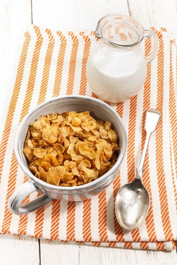 Flocos de milho em uma caneca cinzenta na toalha de cozinha fotografia de stock royalty free