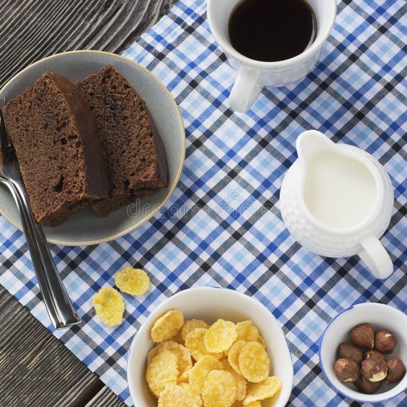 Flocos de milho saudáveis do café da manhã, leite, copo do café preto e bolo de chocolate da fatia imagens de stock