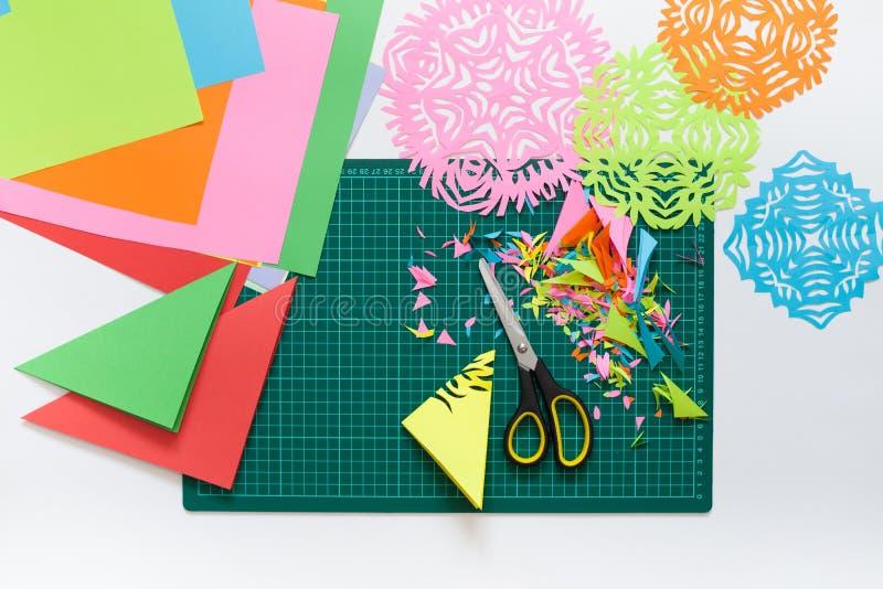 Flocos de neve do papel colorido Tesouras e esteira do corte fotografia de stock