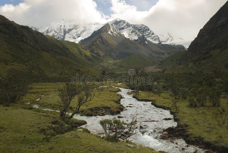 Flod av smältt vatten av den Tullparahu glaciären som flödar ner dalen av Quillcayhuance, Peru arkivfoto