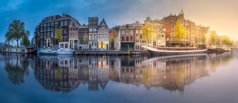 Flod, kanaler och traditionella gamla hus Amsterdam royaltyfri bild
