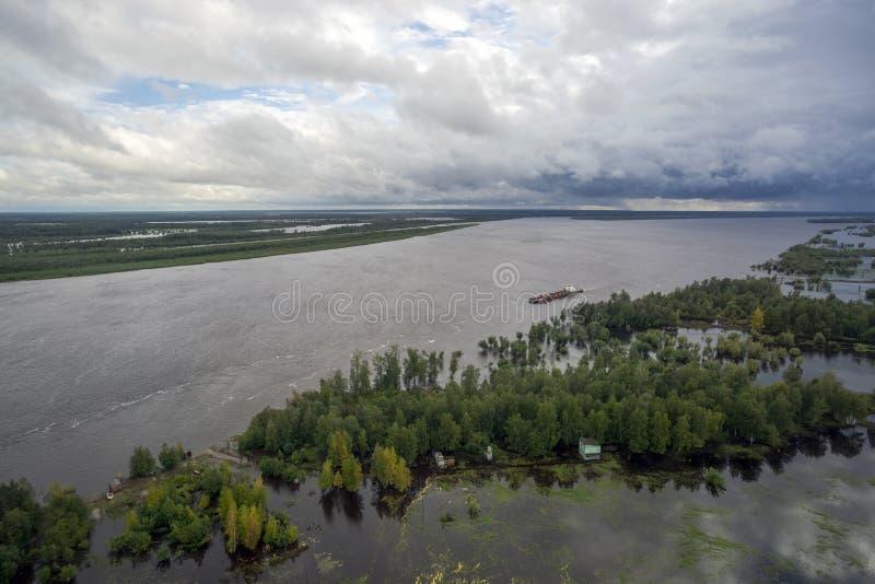 Flod med översvämmade områden Pråm bär royaltyfri foto