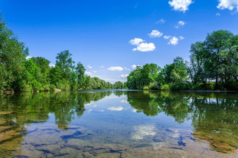 Flod med reflexioner av träd och moln royaltyfria bilder