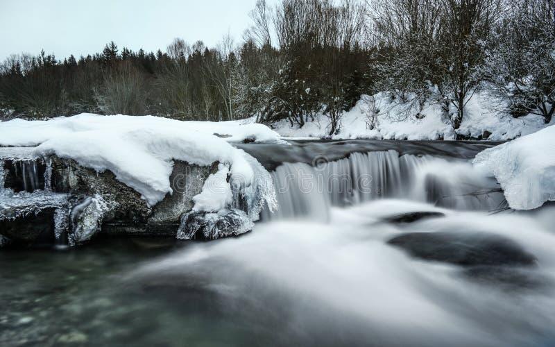Flod som täckas med snö och is i vintern, lång exponering med mjölkaktigt slätt vattenflöde royaltyfri bild