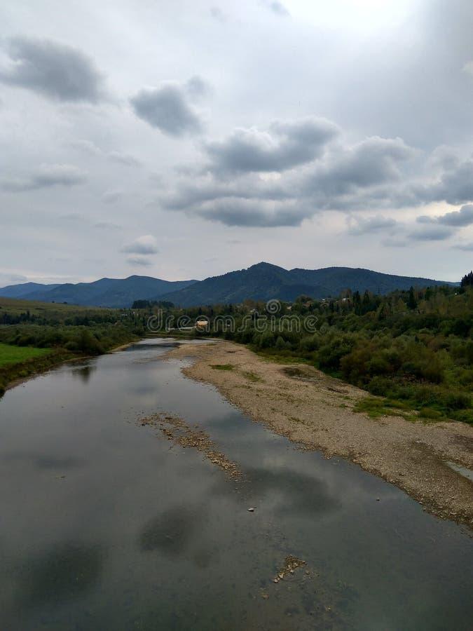 Floden flödar i bergskog fotografering för bildbyråer