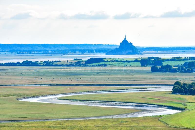 Floden gör dess väg mellan fält och jordbruksmark upp till Mont Saint Michel fotografering för bildbyråer