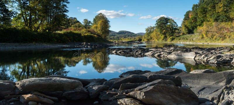 Floden med vaggar i förgrunden och reflexionen av nedgånglandskap arkivbilder