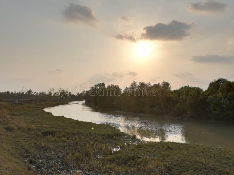 floden och solen sitter royaltyfria bilder