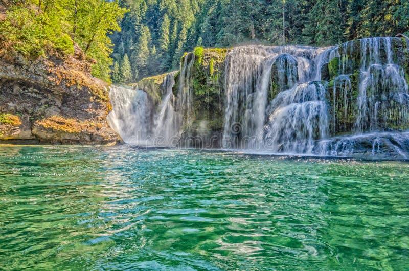 Floden som över applåderar, vaggar in i en pöl för smaragdgräsplan royaltyfria foton